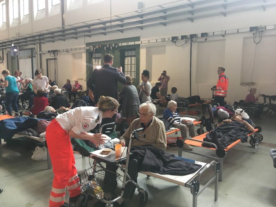 Blick in die Notunterkunft mit Sanitätern die sich um die Evakuierten kümmern, © Sachsen Fernsehen
