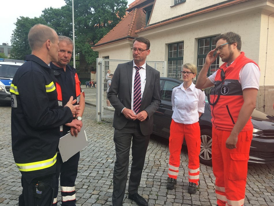 Innenminister Roland Wöller hört sich die Situation der Rettungskräfte vor Ort an, © Sachsen Fernsehen